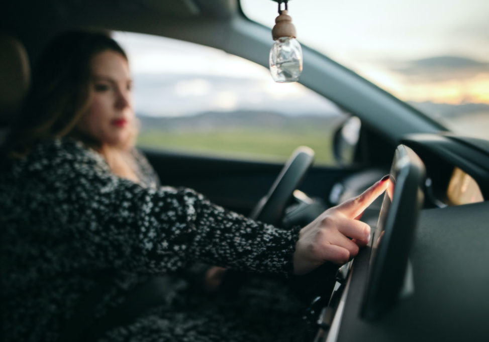 Detail of a woman touching with her finger a car's touch screen