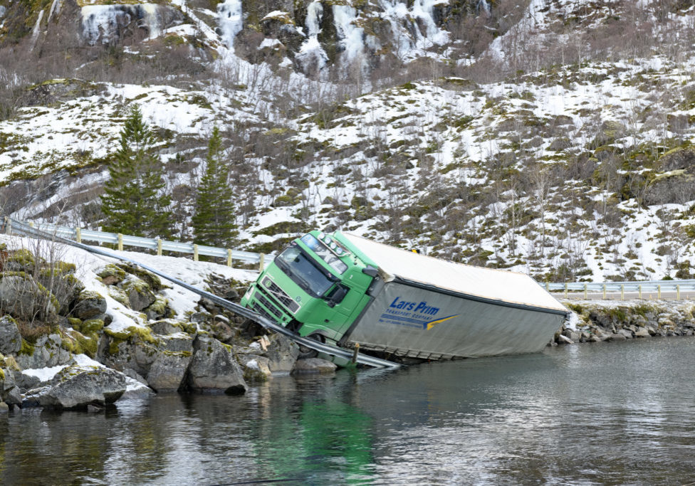 Crashed truck next to a road in a Fjord after an accident in Northern Norway. The truck has crashed through the safety barrier and driven into the cold freezing water of the Fjord next to the E10 road on the Lofoten islands in Northern Norway in winter .